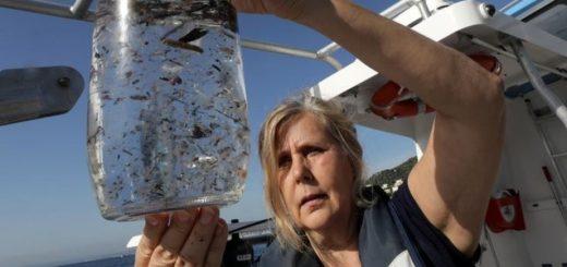 bote cristal con agua y multitud plásticos flotando en ella